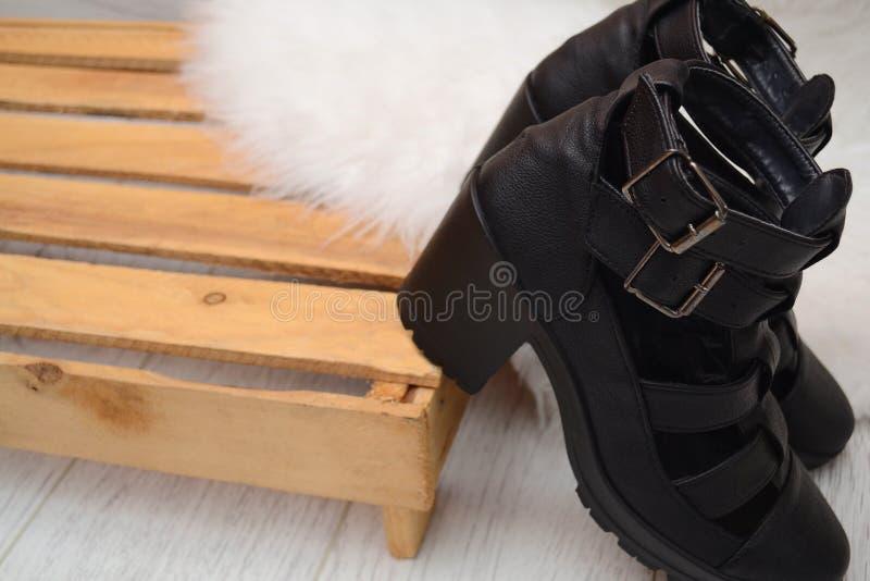Arbeiten Sie Konzept, weibliche Schuhe des Schwarzen mit Schnallen auf der Holzkiste, Raum für Text um stockbild