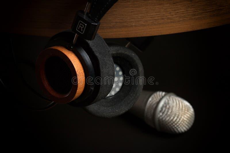 Arbeiten Sie Kopfhörer auf einem hölzernen Stand- und Studiomikrofon auf einem schwarzen Hintergrund um lizenzfreie stockfotografie