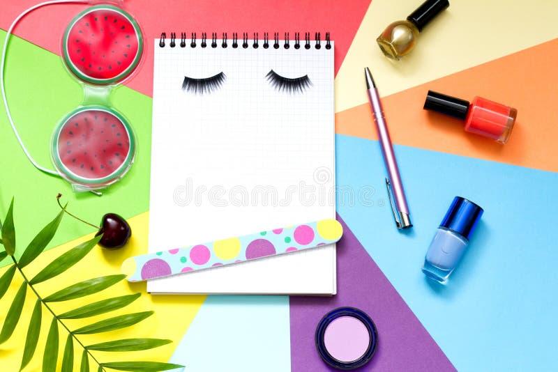 Arbeiten Sie Kosmetikschönheitszusammenfassungslebensstil-Bloghintergrund mit Notizbuch und Zubehör um stockfoto