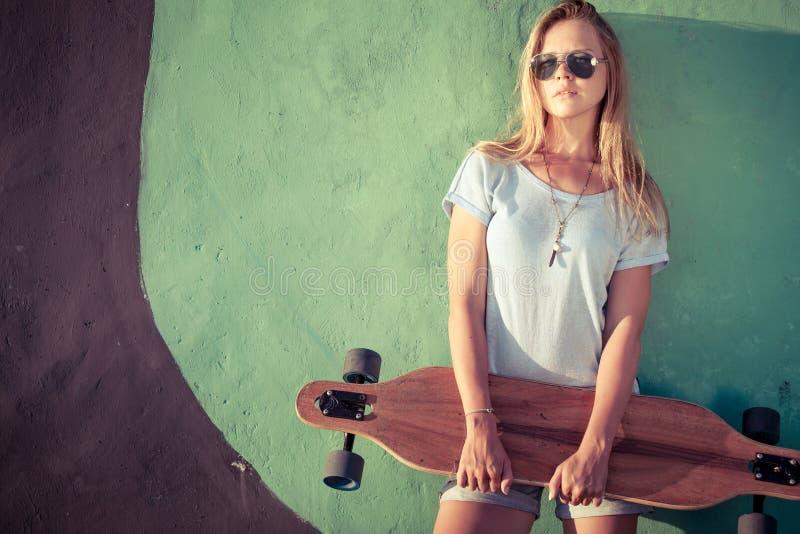 Arbeiten Sie Lebensstil, schöne junge Blondine mit Skateboard um lizenzfreie stockfotos