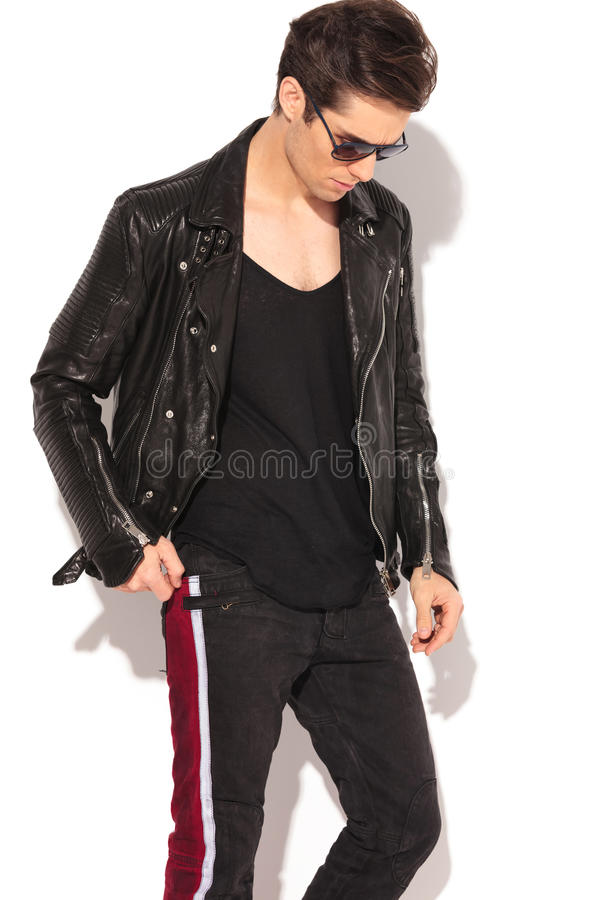 Arbeiten Sie Mann in der Lederjacke und in Sonnenbrille um, die unten schauen lizenzfreies stockfoto