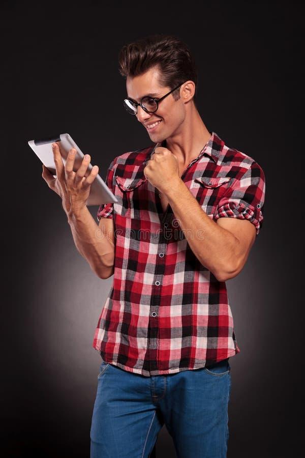 Arbeiten Sie Mannmesswert auf einer Tablette und einem Gewinnen um lizenzfreie stockfotografie