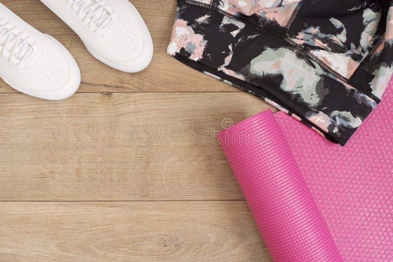 Arbeiten Sie modische Trainer und Gamaschen, rosa Yogamatte um Hippie-Satz Weibliche Turnschuhe, Sportschuhe in der Ebene legen A lizenzfreie stockfotos
