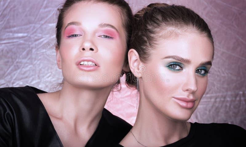 Arbeiten Sie Nahaufnahmeporträt von zwei schönen jungen Frauen um Helles Berufsmake-up stockfotos