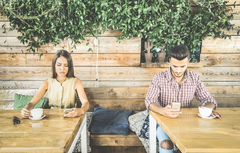 Arbeiten Sie Paare im Desinteressemoment um, der unter Verwendung des Telefons sich ignoriert lizenzfreie stockbilder