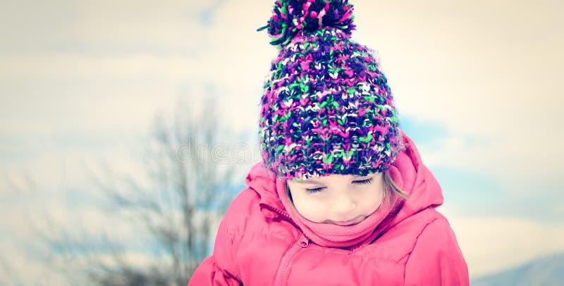 Arbeiten Sie portait eines kleinen Mädchens in der Winterkleidung um, die Spaß herein hat lizenzfreies stockfoto