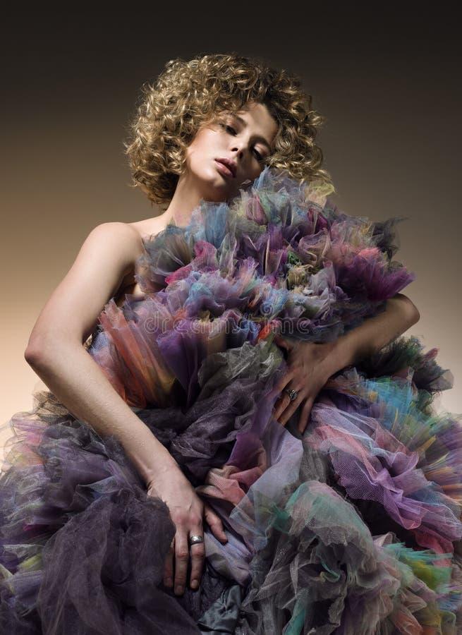 Arbeiten Sie Porträt der jungen Frau mit dem gelockten Haar und einem geschwollenen Kleid um stockfotografie