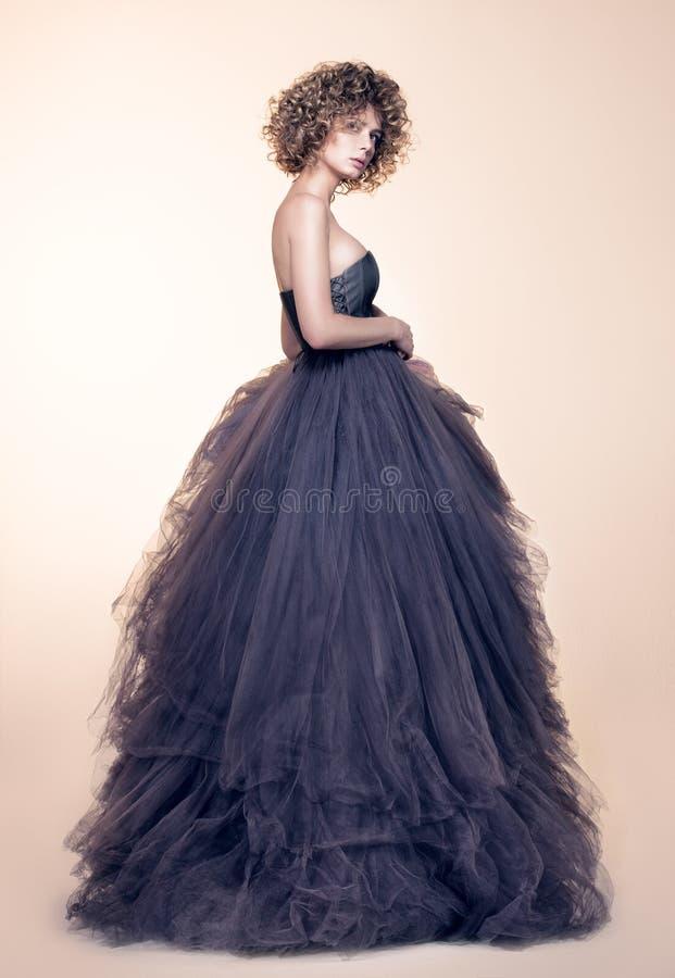 Arbeiten Sie Porträt der schönen jungen Frau in einem langen grauen Kleid um stockbild