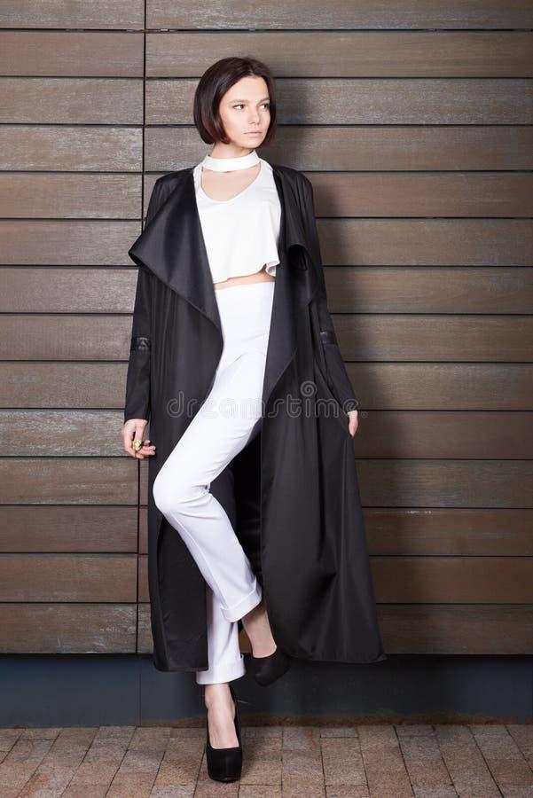 Arbeiten Sie Porträt der schönen jungen Frau in einem langen schwarzen Mantel um lizenzfreie stockfotografie