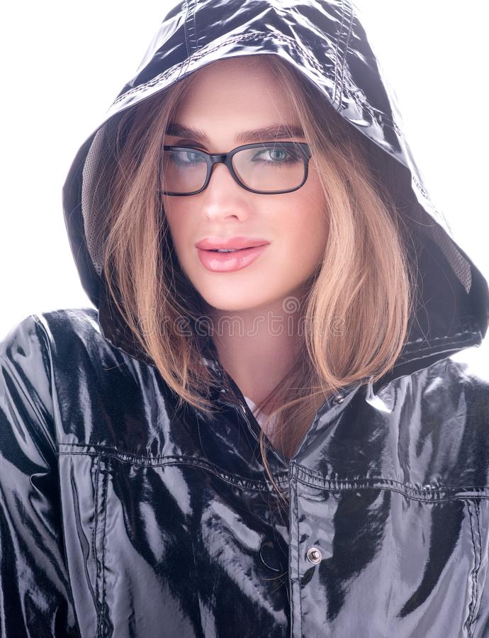 Arbeiten Sie Porträt der schönen jungen Frau mit Gläsern um Glatter schwarzer Mantel mit einer Haube lizenzfreie stockfotografie
