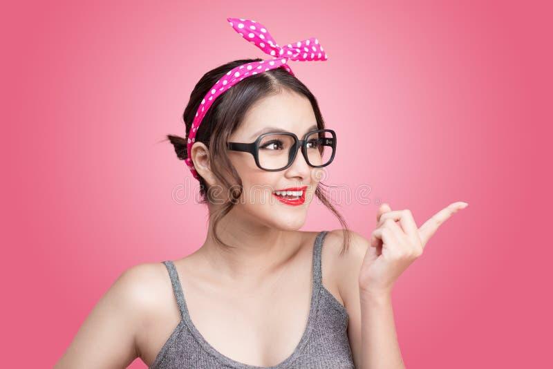 Arbeiten Sie Porträt des asiatischen Mädchens mit der Sonnenbrille um, die auf Rosa steht lizenzfreie stockfotografie