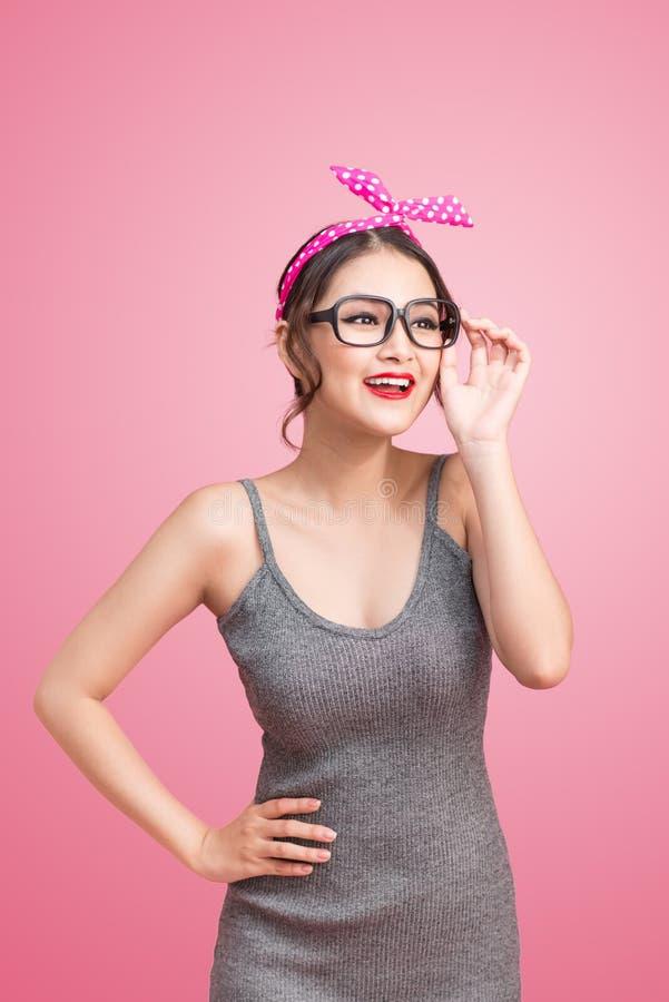 Arbeiten Sie Porträt des asiatischen Mädchens mit der Sonnenbrille um, die auf Rosa steht lizenzfreies stockbild
