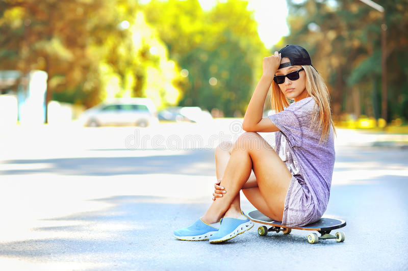 Arbeiten Sie Porträt des attraktiven Mädchens mit einem Skateboard um stockfoto
