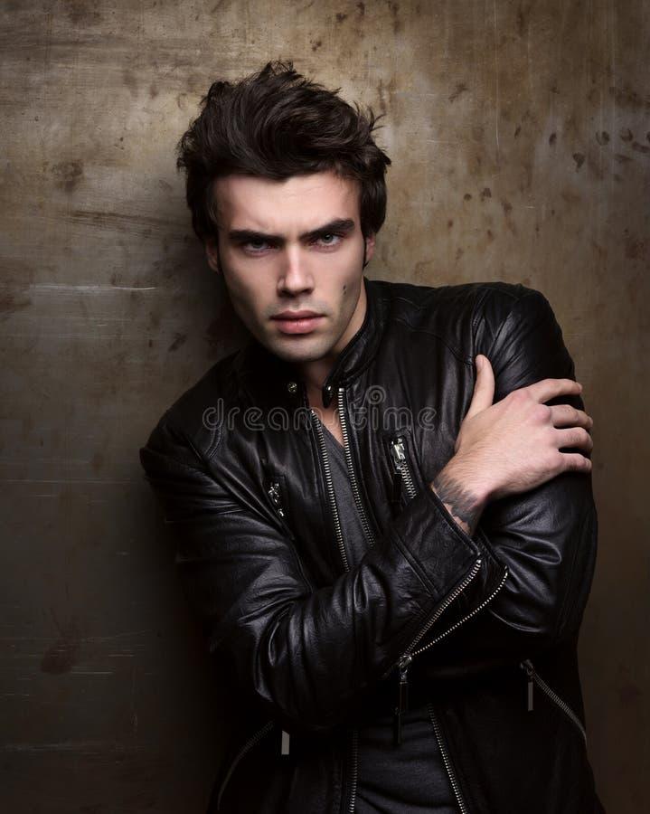 Arbeiten Sie Porträt des hübschen jungen Mannes in einer schwarzen Lederjacke um stockfoto