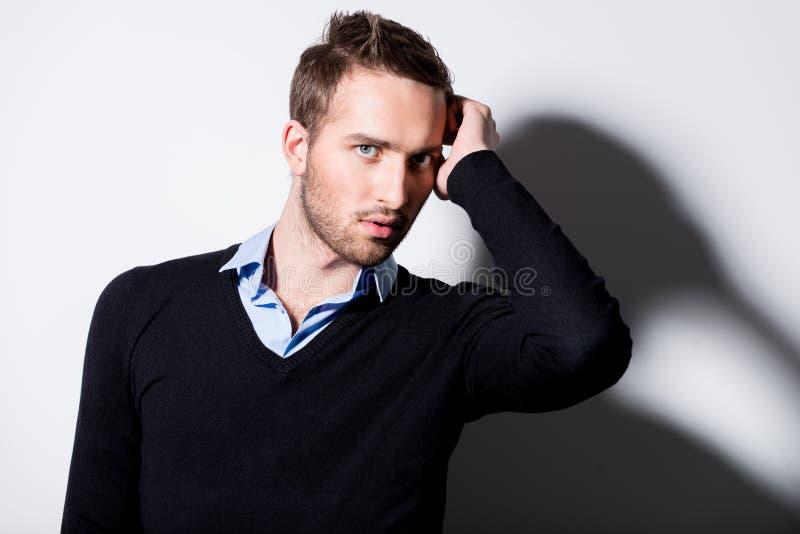 Arbeiten Sie Porträt des jungen Mannes im schwarzen Pullover um. stockfoto
