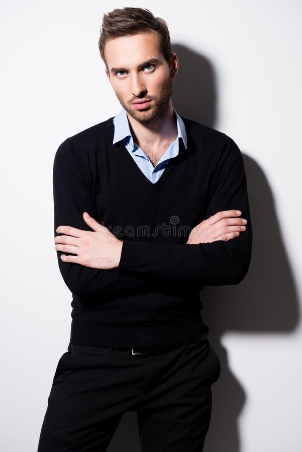 Arbeiten Sie Porträt des jungen Mannes im schwarzen Pullover um. stockfotos