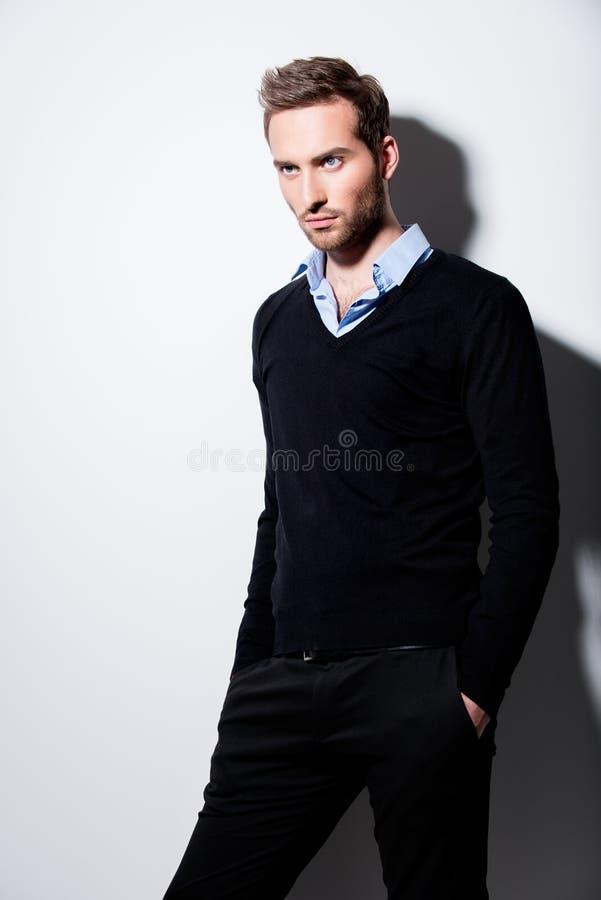 Arbeiten Sie Porträt des jungen Mannes im schwarzen Pullover um. lizenzfreies stockbild