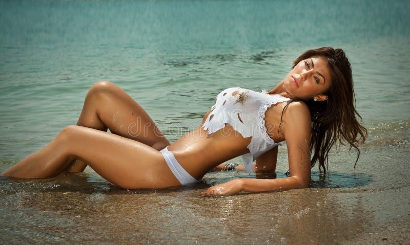 Arbeiten Sie Porträt des jungen sexy Brunettemädchens im Bikini und im nassen T-Shirt am Strand um stockfotografie