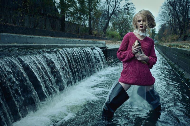 Arbeiten Sie Porträt des Modells im langen Pullover mit toten Fischen in ihren Händen um, die im Fluss des Abwassers gegen Wasser stockfotos
