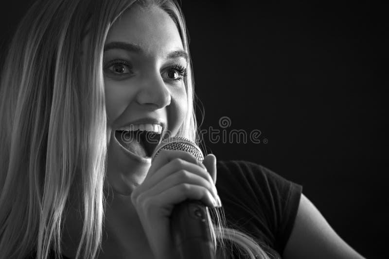 Arbeiten Sie Porträt einer Frau um, die mit einem drahtlosen Mikrofon singt stockfotografie