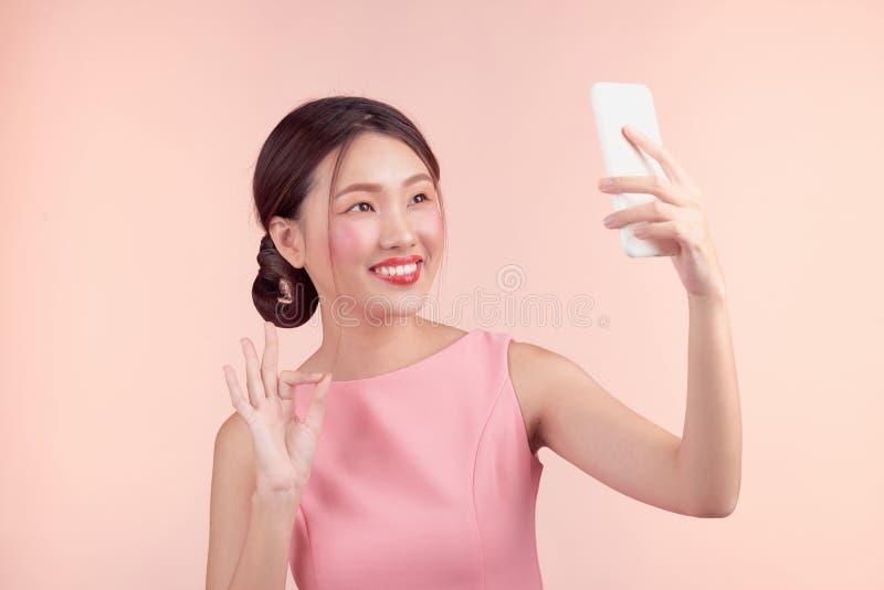 Arbeiten Sie Porträt einer schönen jungen Frau in einem hübschen Kleid über rosa Hintergrund um stockfotos