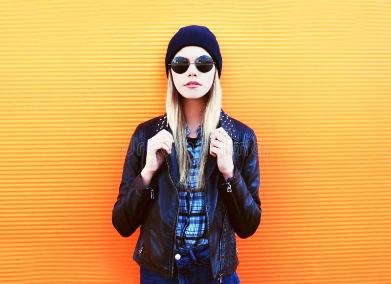 Arbeiten Sie Porträt hübsche Blondine in der Felsenschwarzart auf einem bunten orange Hintergrund um stockfotografie