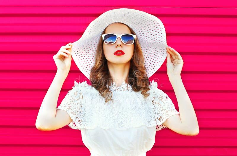 Arbeiten Sie Porträt hübsche Frau im weißen Sommerstrohhut über buntem Rosa um stockbild