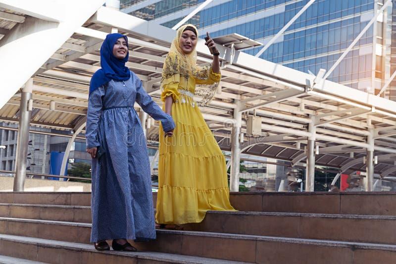 Arbeiten Sie Porträt junge schöne moslemische Frau zwei tragenden hij um stockbilder