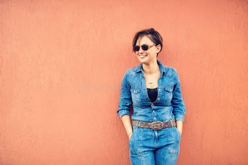 Arbeiten Sie Porträt mit schöner lustiger Frau auf der Terrasse um, die moderne Jeans Ausstattung, Sonnenbrille und Lächeln trägt lizenzfreies stockbild