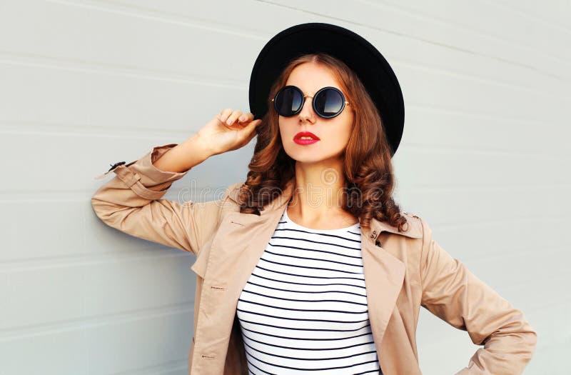Arbeiten Sie Porträt schöne junge Frau mit den roten Lippen um, die Sonnenbrillemantel des schwarzen Hutes über grauem Hintergrun lizenzfreie stockfotografie