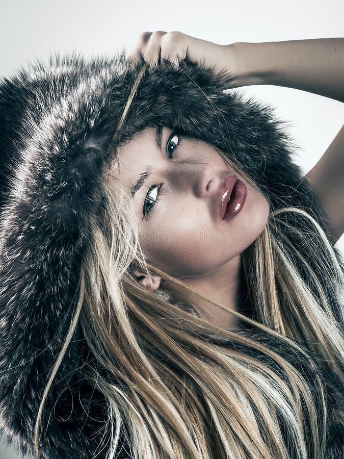 Arbeiten Sie Porträt von attraktiven Blondinen in der Pelzmantelhaube um stockbild