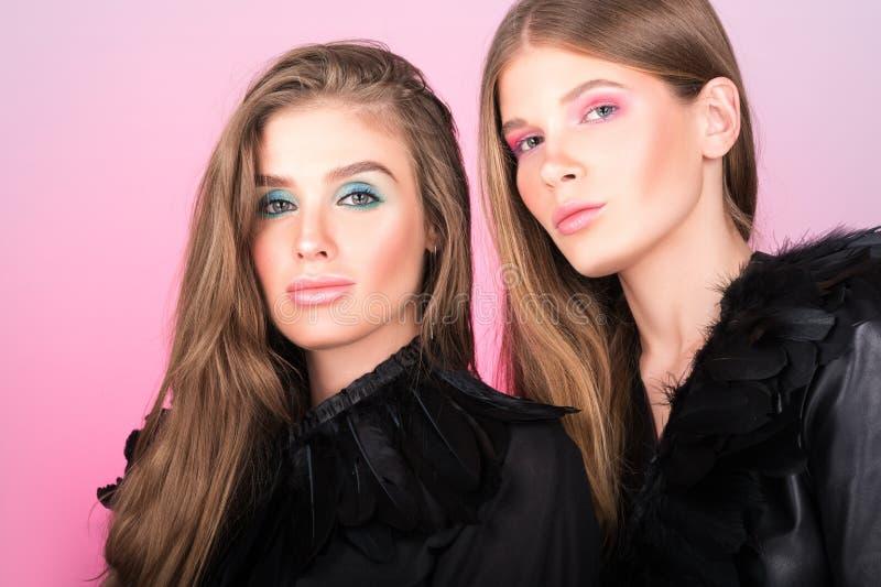 Arbeiten Sie Porträt von zwei schönen jungen Frauen im Schwarzen um Helles Berufsmake-up lizenzfreie stockfotografie