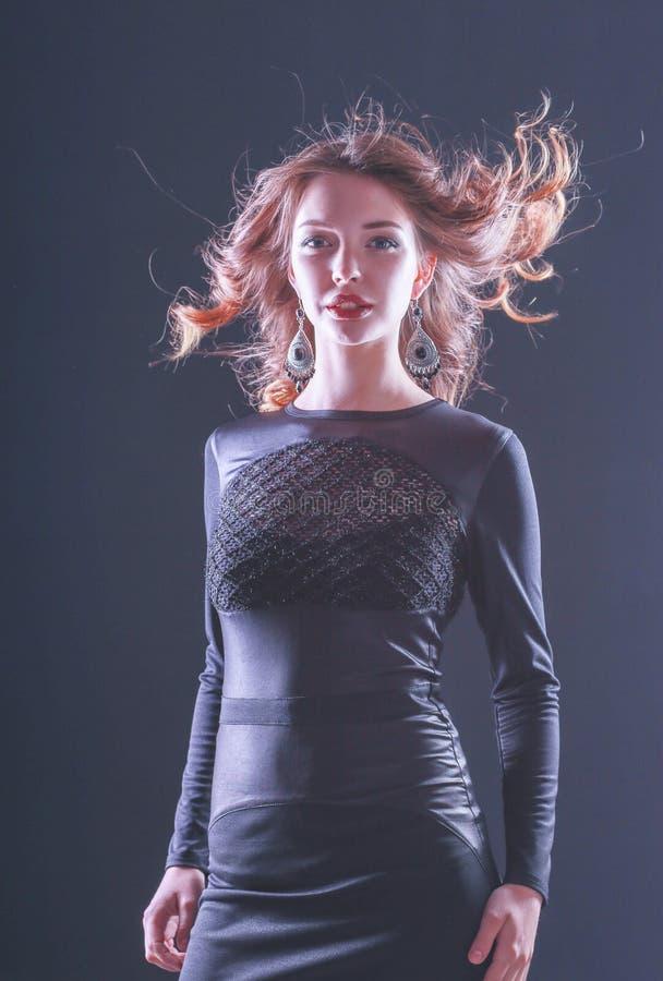 Arbeiten Sie Portr?t von sch?nem vorbildlichem Girl um, das schwarzes Kleid tr?gt lizenzfreies stockbild
