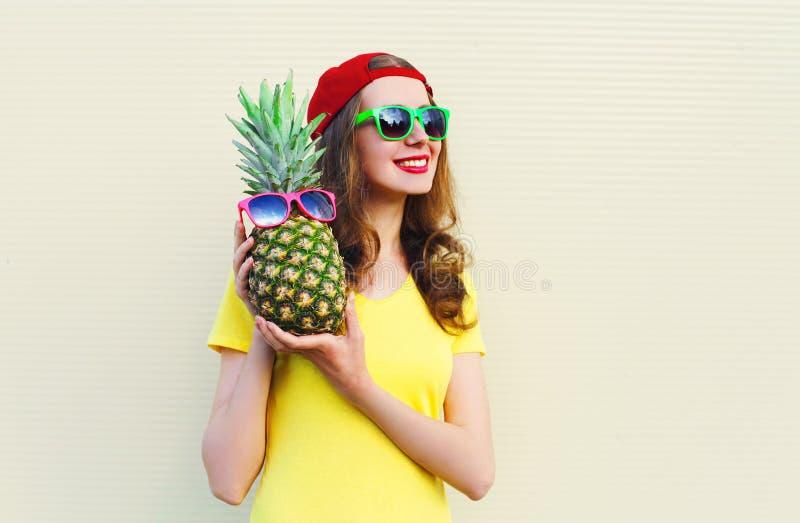 Arbeiten Sie recht glückliches lächelndes Mädchen mit Ananas über Weiß um lizenzfreie stockfotos