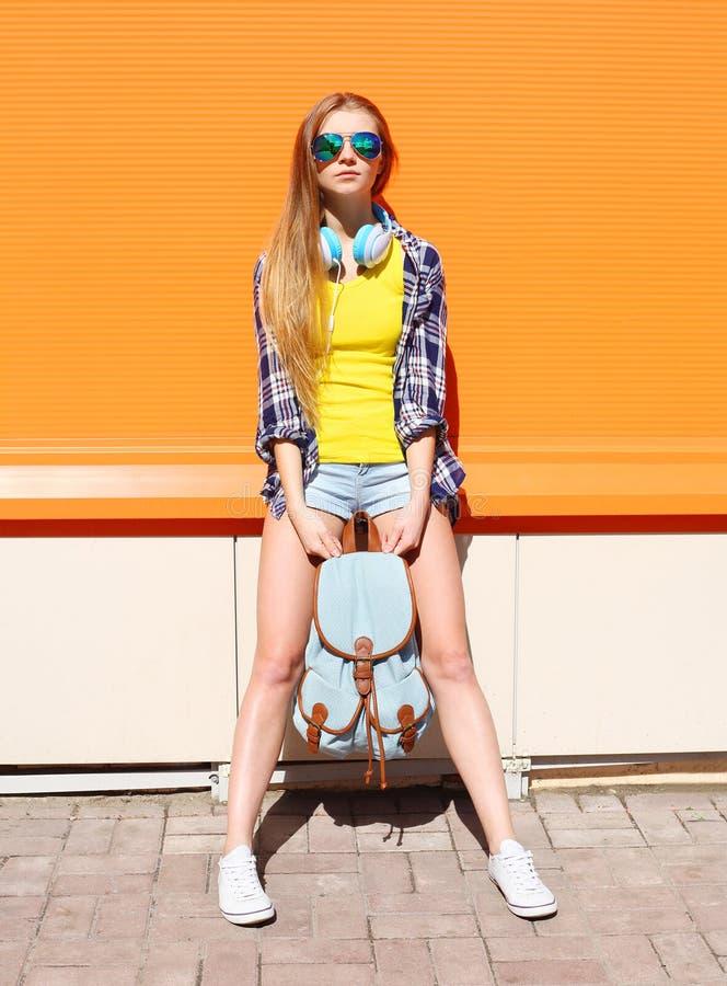 Arbeiten Sie recht kühles Mädchen in der Sonnenbrille mit Rucksack und Kopfhörern über Orange um stockbild