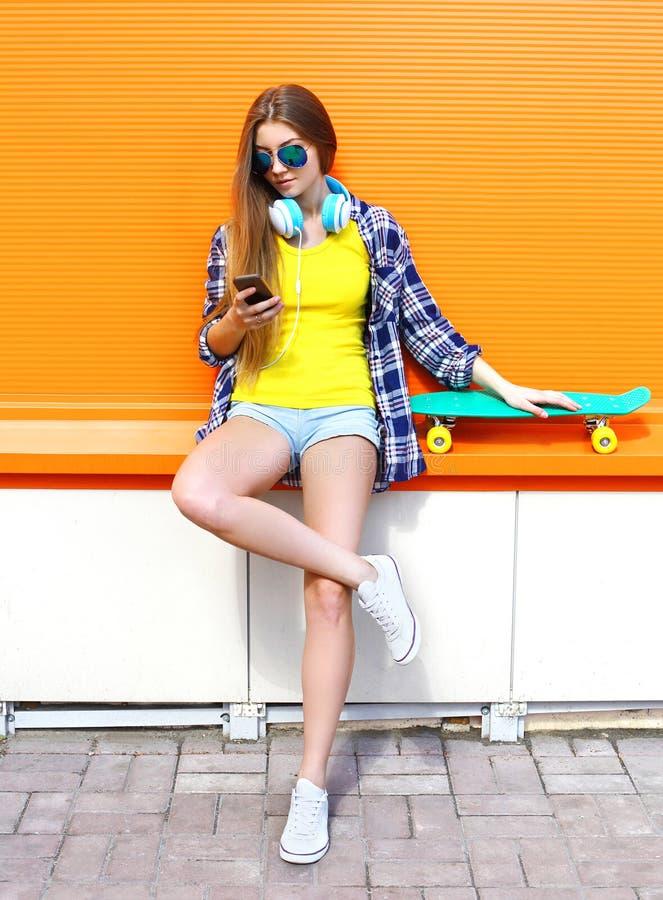 Arbeiten Sie recht kühles Mädchen mit Kopfhörern und Skateboard unter Verwendung des Smartphone in der Stadt über bunter Orange u lizenzfreie stockbilder