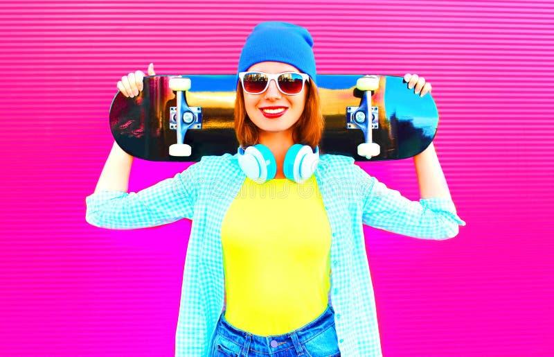 Arbeiten Sie recht lächelnde Frau mit einem Skateboard in der Stadt auf Rosa um stockfoto