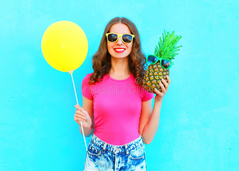 Arbeiten Sie recht lächelnde Frau mit gelbem Luftballon und -ananas um, die rosa T-Shirt über buntem blauem Hintergrund trägt stockfotos