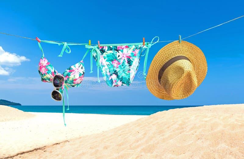 Arbeiten Sie Sommerbadeanzugbikini, Sonnenbrille und großen Hut auf Seil um Stilvoller Strandsatz des Sommerbikinis und der Ausst stockfoto