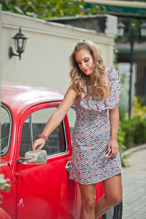 Arbeiten Sie städtisches Porträt des schönen Modells mit den langen Beinen auf der Straße um Blondes Mädchen mit kurzem Kleid lizenzfreie stockfotos