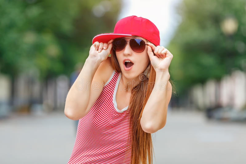 Arbeiten Sie Stadtporträt der stilvollen Hippie-Frau, des roten gestreiften Kleides, der roten Kappe und der Turnschuhe, Make-up, stockbild