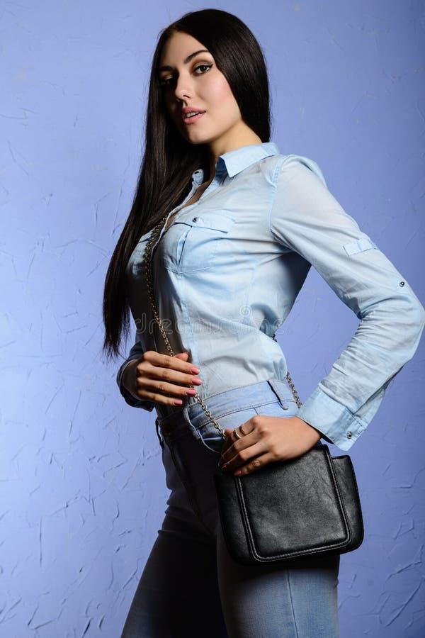 Arbeiten Sie stilvolles Brunettemädchen in den Jeans um, welche die Kamera betrachten lizenzfreie stockfotos