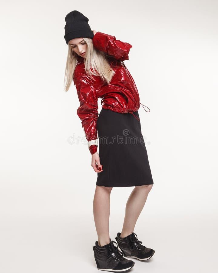 Arbeiten Sie Studiofoto der Frau in der roten Jacke und im schwarzen Rock auf w um stockfotografie