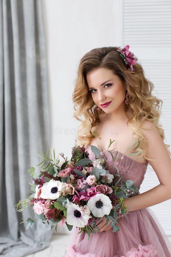 Arbeiten Sie Studiofoto des schönen jungen Mädchens mit dem langen gelockten Haar in einem rosa Kleid und in den Blumen um stockbild