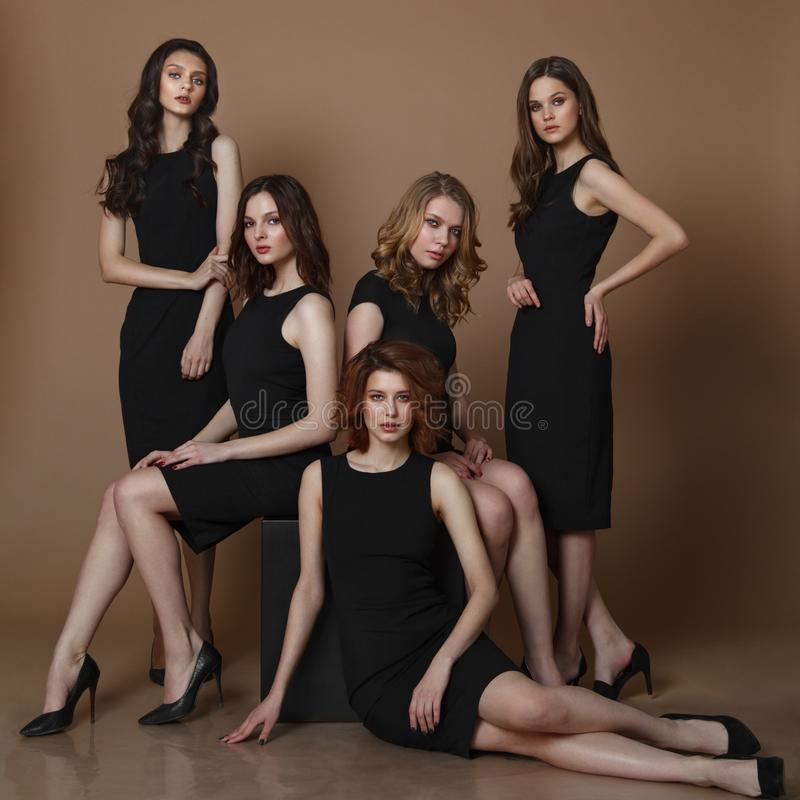Arbeiten Sie Studiofoto von fünf elgant Frauen in den schwarzen Kleidern um lizenzfreie stockfotos
