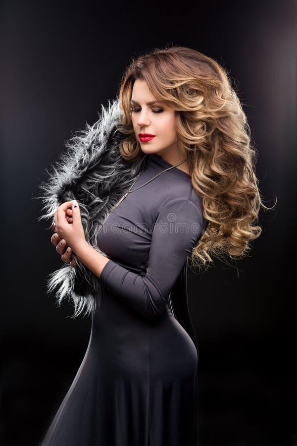 Arbeiten Sie Studioporträt der Schönheit in einem grauen Kleid mit curvy Zahlen um lizenzfreies stockbild