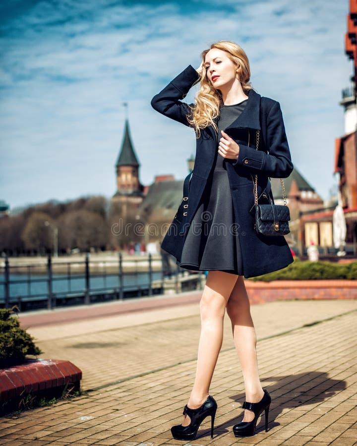 Arbeiten Sie tragenden Mantel des Mädchens, Handtasche und schwarze dressin Stadt um stockbilder