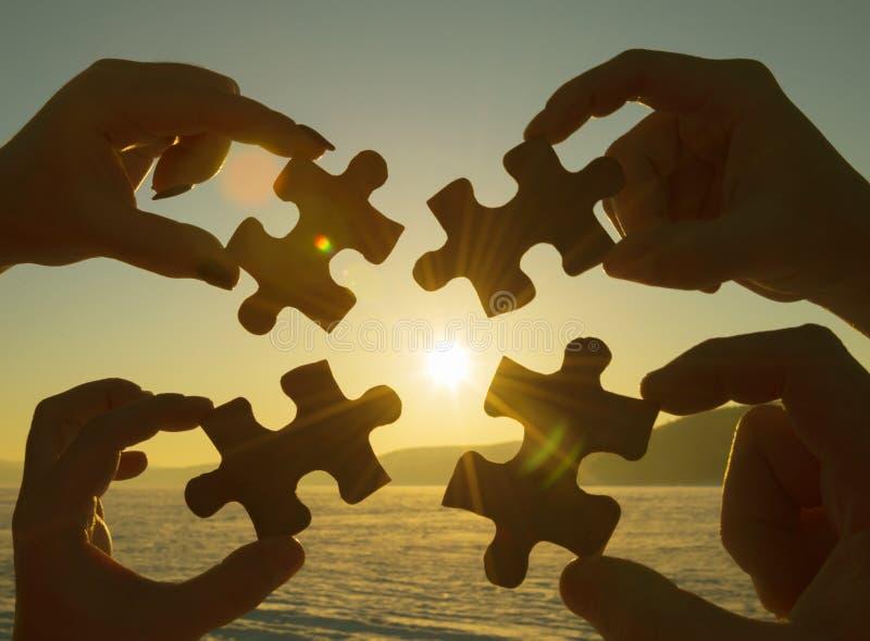 Arbeiten vier Hände zusammen, die versuchen, ein Puzzlespielstück mit einem Sonnenunterganghintergrund anzuschließen stockfotografie