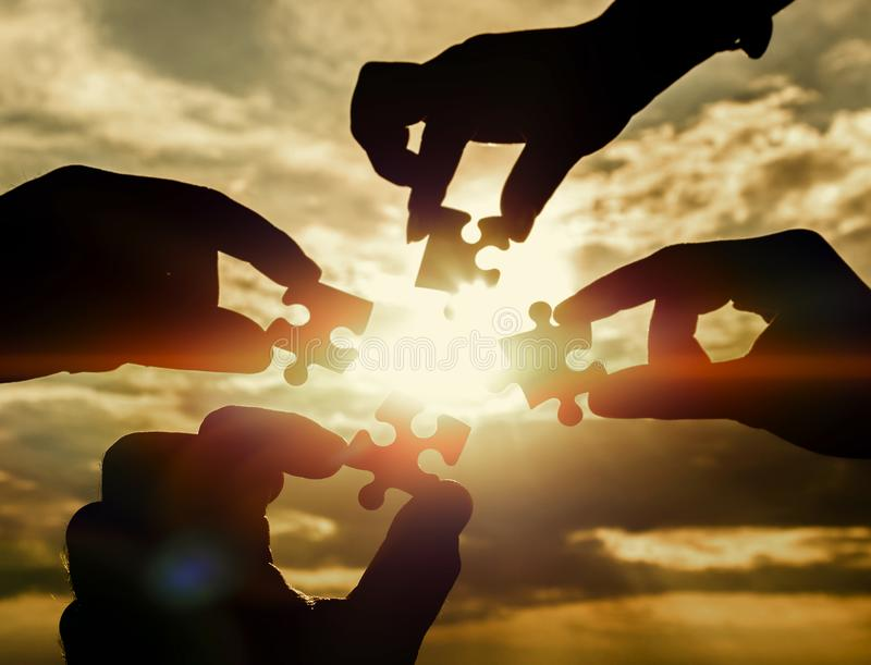 Arbeiten vier Hände zusammen, die versuchen, ein Puzzlespielstück mit einem Sonnenunterganghintergrund anzuschließen stockfotos