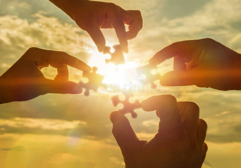 Arbeiten vier Hände zusammen, die versuchen, ein Puzzlespielstück mit einem Sonnenunterganghintergrund anzuschließen stockbilder